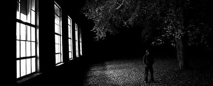 Silhouette devant des fenêtres éclairées la nuit