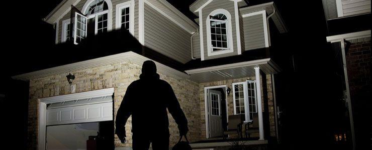 Cambrioleur devant une maison ouverte
